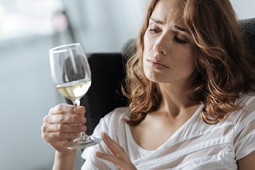 Woman with wine glass who wants to stop drinking but is scared of the alcohol withdrawal timeline